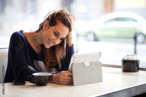 Candid image of a young woman using tablet computer in a coffee