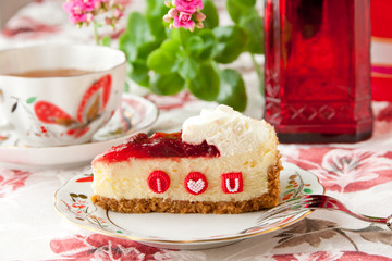 Piece of strawberry cheesecake with edible letters for Valentine