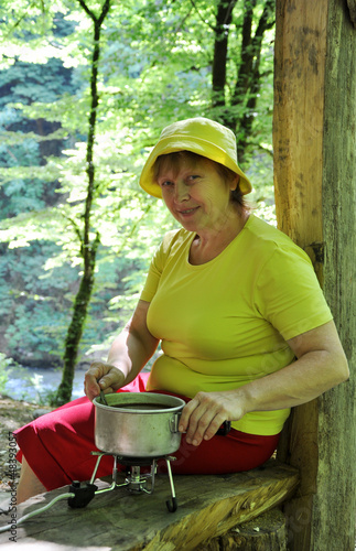 A middle-aged female tourists makes coffee in camp
