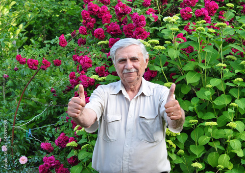 An elderly white-haired man in a garden