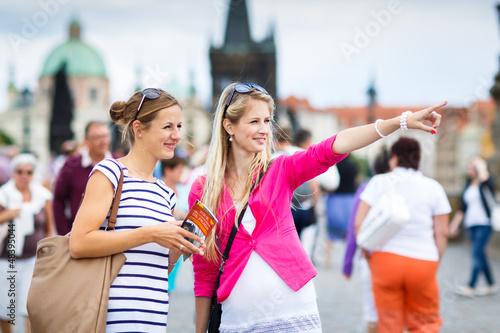 Two female tourists walking along the Charles Bridge