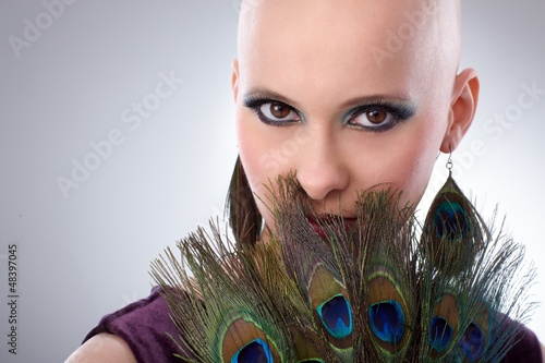 Bald woman with peacock plumes