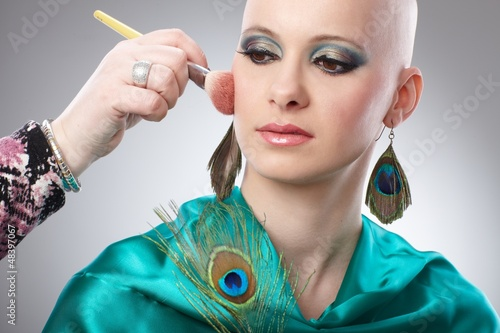 Bald woman getting makeup