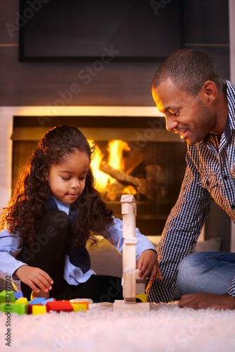 Ethnic father and daughter playing together