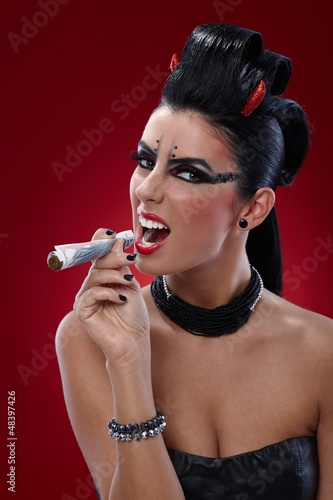 Wicked woman smoking banknotes