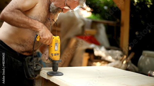 Senior man sanding a piece of wood