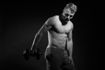 Muscled fitness man holding dumbell. Black and white shot.
