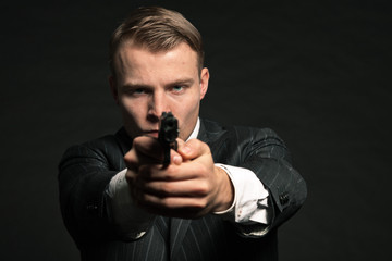 Man in suit shooting with gun. Studio shot against black.