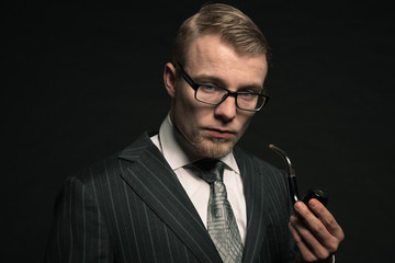 Fashion man in suit with glasses and pipe. Studio shot.