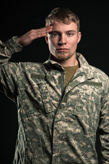 Military young man salutes. Studio portrait.