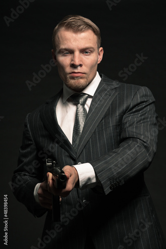 Mafia man in suit with cocaine and rifle. Studio shot.