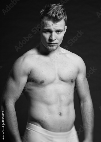 Muscled fitness man. Black and white studio shot.