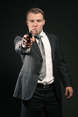 Man in suit shooting with gun. Smoking cigarette. Studio shot.