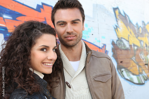 young couple in front of a graffiti wall