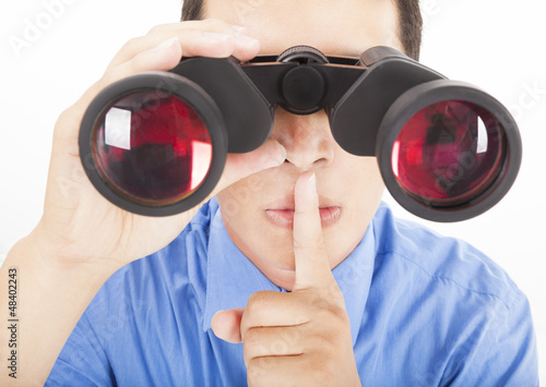 man looks through binoculars with silent gesture
