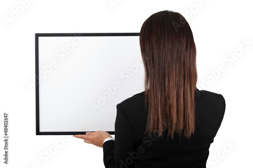 Woman back at the camera holding a frame.