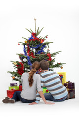 Couple sitting in front of a Christmas tree