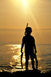 Boy silhouette with the sunshine in the bottom