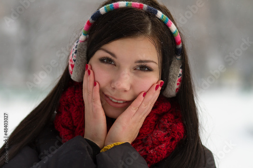 Girl in earplugs outdoors in winter