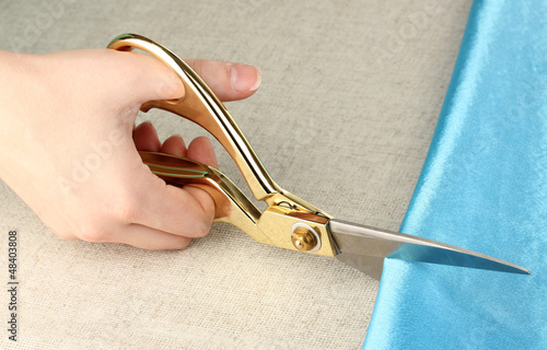 Seamstress cut blue fabric on beige fabric background