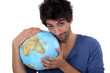 Handsome man hugging a globe