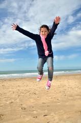 Niña saltando en la playa