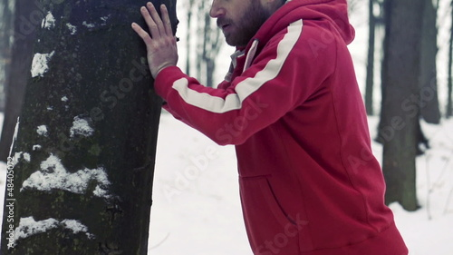 Man exercising by tree in winter, super slow motion