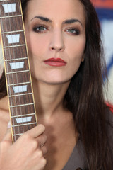 Unfriendly woman posing with her guitar