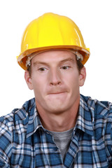 A portrait of a construction worker biting his lips.