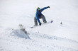Young male snowboarder jumping on a snowy slope