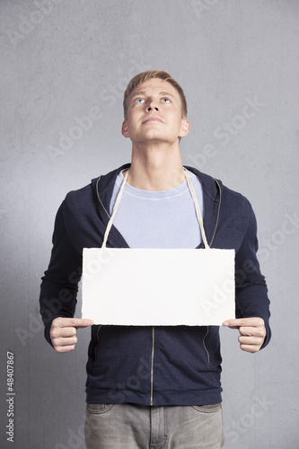 Pleased likable man holding empty signboard.
