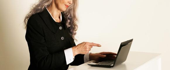 Frau zeigt in Laptop