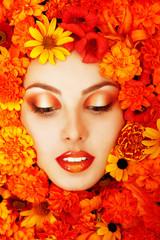 beauty portrait of beautiful female face with orange flowers
