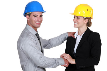 Male and female architects shaking-hands