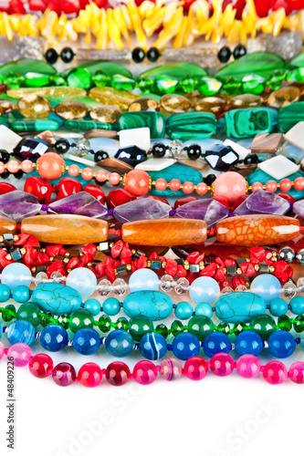 Lot of colored beads from different minerals and stone backgroun