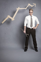 Confident businessman with wrench and graph.
