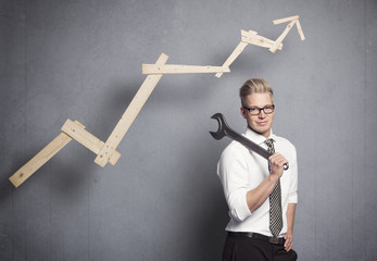 Smiling businessman with wrench and graph.