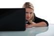 Blond woman peering from behind laptop