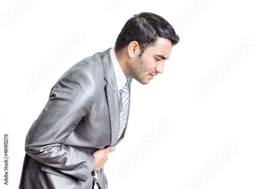Business man with stomach ache with hands on abdomen