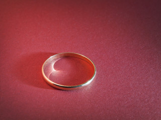 gold ring on red paper background abstract