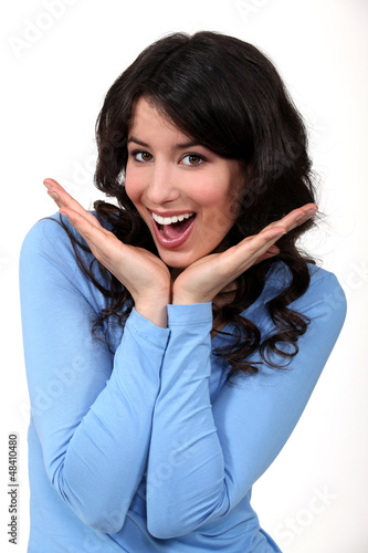 Excited woman holding hands to her face in delight