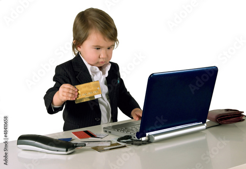 One small little girl (boy) with phone, computer and credit card
