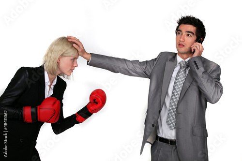 businesswoman with boxing gloves and colleague on phone