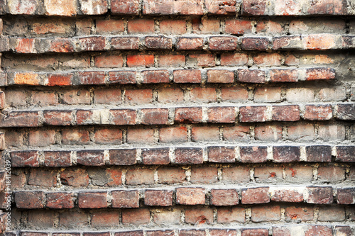 Old grunge wall with indented bricks