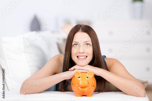 junge frau stützt sich auf ihr sparschwein