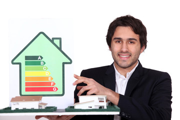Architect holding model house and energy rating card