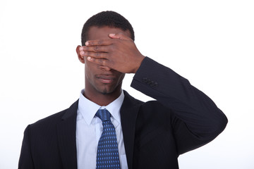 Businessman covering eyes with hand