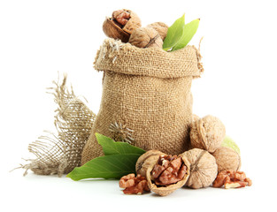 walnuts with green leaves in  burlap bag, isolated on white