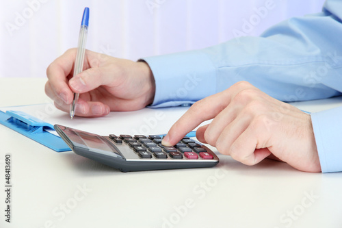 Closeup of businessman hands with calculator