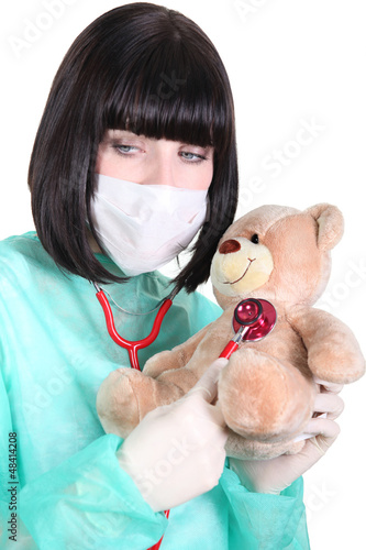 Doctor listening to the heartbeat of a teddy bear